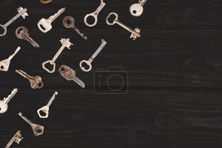 top view of different vintage keys on black table