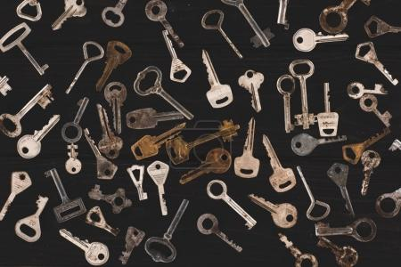 Photo for Top view of different metal keys on black table - Royalty Free Image