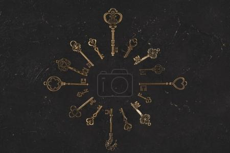 top view of vintage keys forming circle frame on black table
