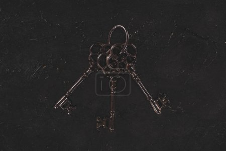 top view of vintage metal bunch of keys on black table