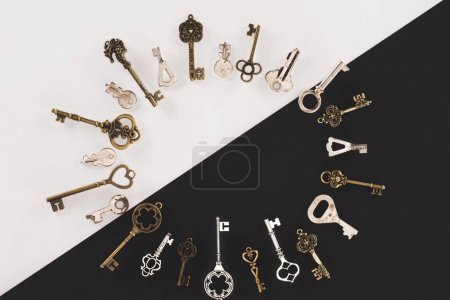top view of different vintage keys circle frame over black and white background