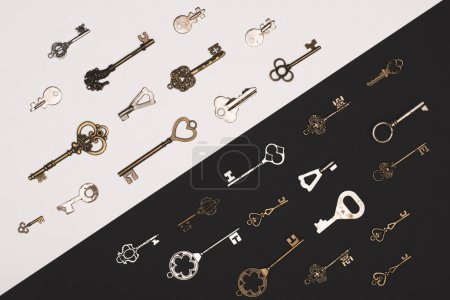 top view of different vintage keys over black and white background