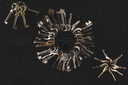 top view bunches of different keys on black table