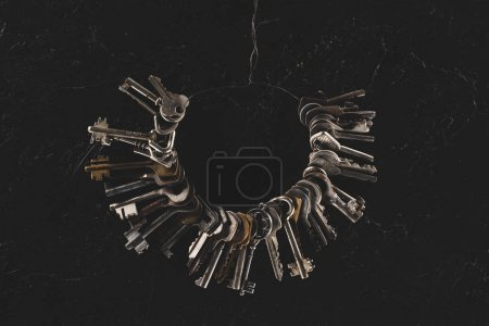 top view of bunch different keys on black table