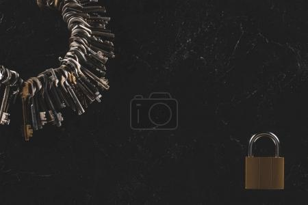 Photo for Top view of heap different metal keys with lock on black table - Royalty Free Image