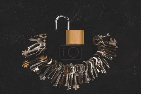 Photo for Top view of heap different metal keys with opened lock on black table - Royalty Free Image