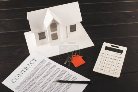 Photo for House buying concept with contract, keys, calculator and maquette over wooden table - Royalty Free Image