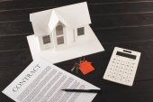 house buying concept with contract, keys, calculator and maquette over wooden table