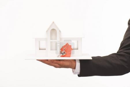 cropped image of hand holding maquette of house with key isolated on white