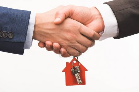 cropped image of shaking hands with key from house isolated on white