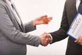 cropped image of costumer and estate agent shaking hands isolated on white