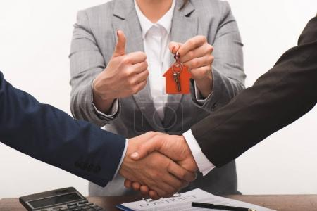 Photo for Cropped image of costumer and estate agent shaking hands, realty buying concept isolated on white - Royalty Free Image