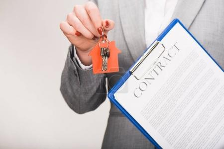 cropped image of estate agent holding keys and contract, house buying concept isolated on white