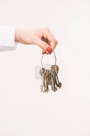 cropped image of female hand holding keys isolated on white