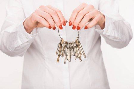 cropped image of female holding keys isolated on white