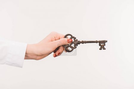 cropped image of female hand holding vintage key isolated on white