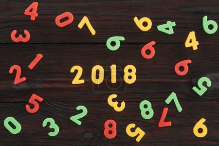 top view of colorful 2018 numbers on dark wooden surface