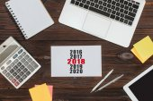 top view of digital devices, office supplies and 2018 calendar on wooden surface