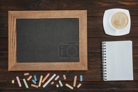 flat lay with empty chalkboard, cup of coffee, blank notebook and chalks on dark wooden tabletop