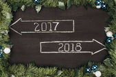 top view of 2017, 2018 year signs with christmas decorations around on dark wooden surface