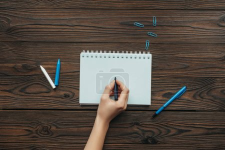 Photo for Partial view of woman with pencil in hand writing in notebook on wooden tabletop - Royalty Free Image