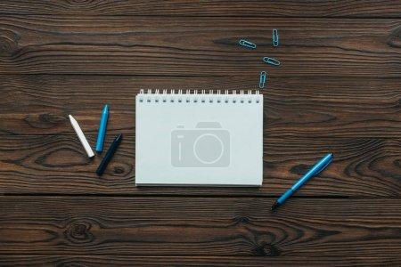 Foto de Vista superior de dispuesto cuaderno, lápices, clips y pluma en tablero de madera - Imagen libre de derechos