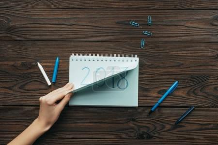 cropped shot of woman tearing notebook paper with 2018 year sign on wooden tabletop
