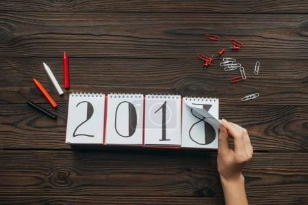 cropped shot of woman tearing calendar part of 2018 year with dark wooden surface as background