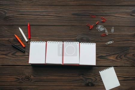 top view of arranged blank calendar, pencils, clips and pins on wooden tabletop