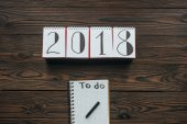 top view of 2018 calendar and notebook with to do lettering on wooden tabletop