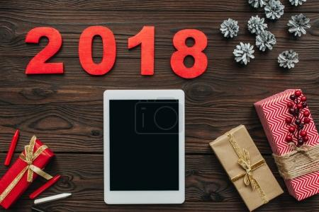 flat lay with tablet, wrapped gifts and 2018 numbers on wooden surface