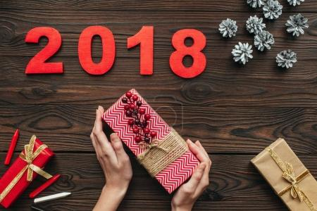 cropped shot of woman holding wrapped gift in hands with pine cons and 2018 around on wooden tabletop
