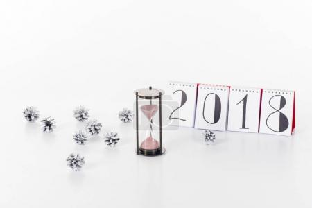 close up view of 2018 calendar, sand clock and pine cones isolated on white