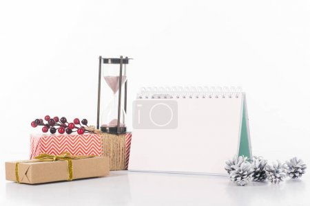close up view of blank calendar, sand clock, pine cones and wrapped gifts isolated on white