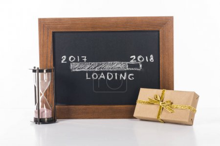 close up view of chalkboard with 2017 to 2018 loading lettering with hourglass and gift near by isolated on white