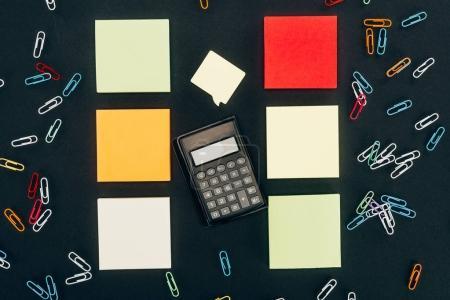 Taschenrechner von oben, bunte Büroklammern und leere Notizen auf schwarz