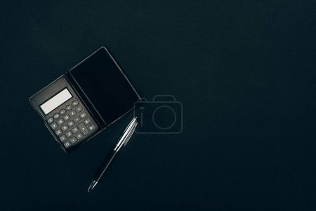 top view of calculator and pen on black background