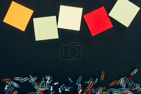 top view of various colorful blank notes and paper clips on black