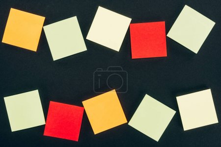 top view of various colorful blank notes on black