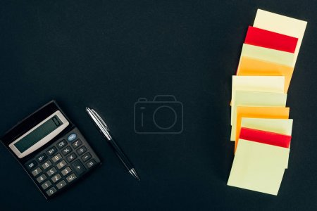 top view of various colorful blank notes, calculator and pen on black
