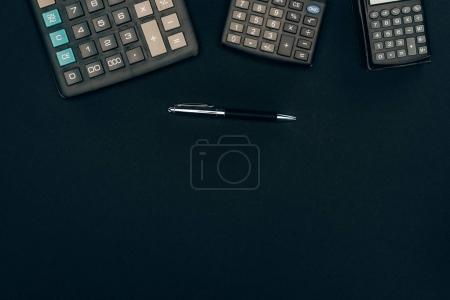 top view of three calculators of different sizes and pen on black