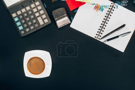 Draufsicht auf Tasse Kaffee, Taschenrechner und Bürobedarf auf schwarz