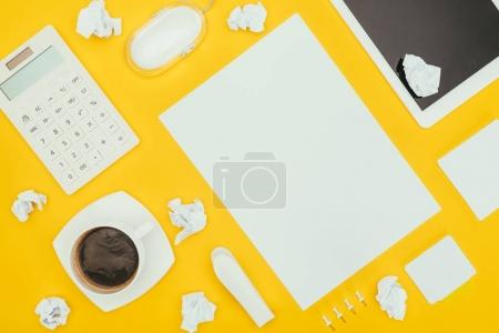top view of blank sheet of paper, crumpled papers, notes, calculator and digital tablet isolated on yellow