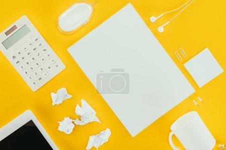 Foto de Vista superior de la hoja en blanco de papel, papeles arrugados, notas, calculadora, auriculares, ratón de ordenador y tableta digital aislado sobre fondo amarillo - Imagen libre de derechos