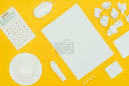 top view of blank sheet of paper, crumpled papers, notes, calculator and computer mouse isolated on yellow
