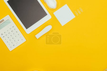 top view of digital tablet with blank screen, calculator and office supplies isolated on yellow