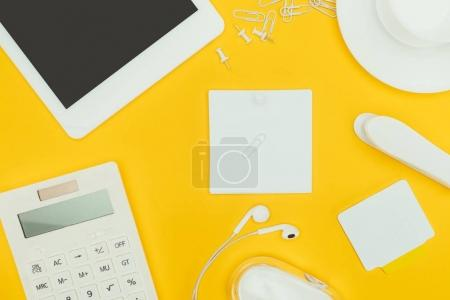 top view of blank papers, calculator, digital tablet and computer mouse isolated on yellow