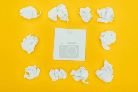 top view of crumpled papers and blank notes isolated on yellow