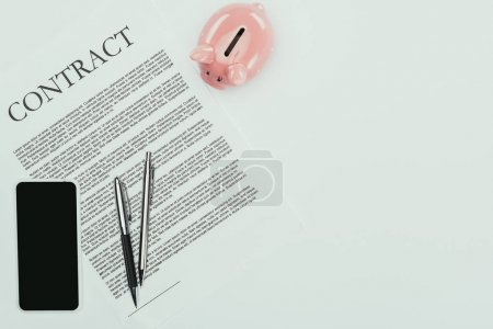 top view of smartphone with blank screen, contract with pens and piggy bank on white