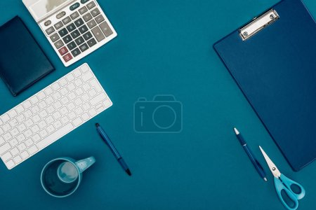 Photo for Top view of clipboard, calculator and office supplies on blue - Royalty Free Image